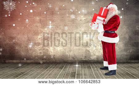 Santa carrying gifts against grimy room
