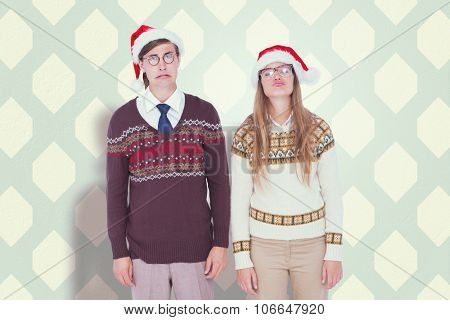 Sad geeky hipster couple against blue and cream patterned wallpaper
