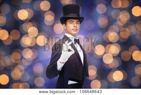 magic, performance, circus, people and show concept - magician in top hat showing ok hand sign over nigh lights background