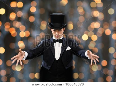 magic, performance, circus, people and show concept - magician in top hat showing trick over nigh lights background