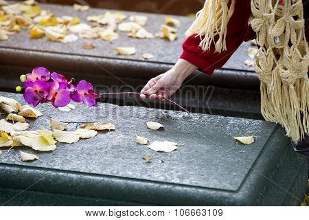 Closeup Of Hand Putting Flower On Grave