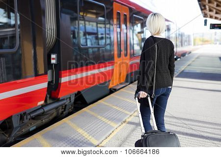 Young woman at a train terminal walks with a wheeled suitcase to a train. Traveling with public transport. poster