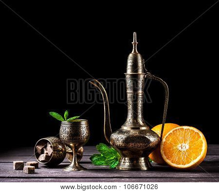 Moroccan tea with mint and oranges in oriental cooper pot and cups on rustic wooden background poster