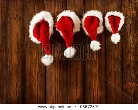 Christmas Family Santa Claus Hats Hanging on Wood Wall Xmas Hat Hang on Decorated Background