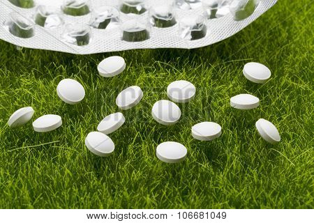 White antibiotic pills and empty blister pack scattered on the green grass poster