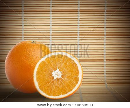 One And Half Oranges On Bamboo Mat Background