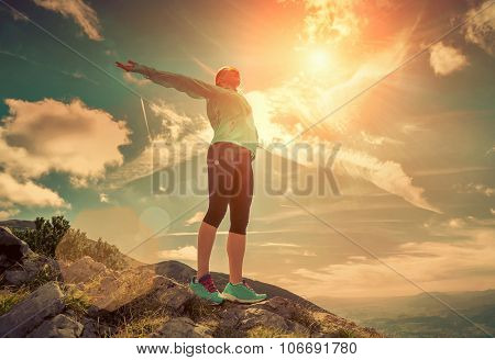 Female stay on the top of mountain under sunlight.