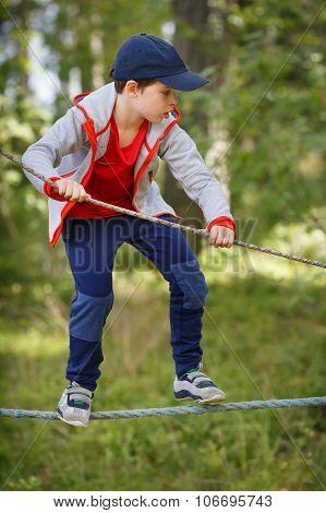 Cute little boy having fun outdoors climbing on playground