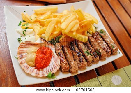 traditional slovenian and croatian cuisine, grilled meat kebab - chevapchichi with french fries, selective focus poster