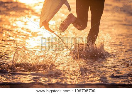 Surfer Running In The Water With His Board
