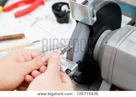 Sharpening the metal cutter on the grinding machine poster