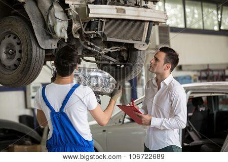assessor analyzing damage crash car with repair man