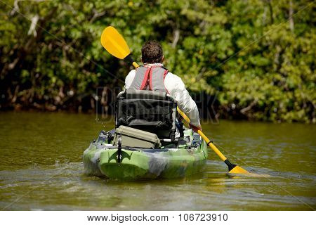 man kayaking in mangroves in florida with paddle
