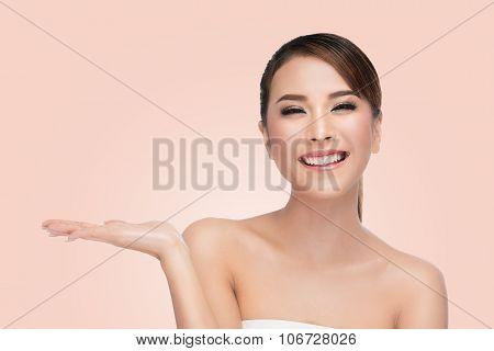 Happy woman presenting with open hand holding something blank,Skin Care Concept.