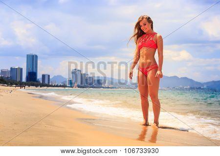 Blonde Slim Gymnast In Bikini Stands Smiles On Edge Of Sea