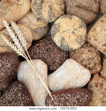 Healthy bread roll assortment with wheat sheaths forming an abstract background.