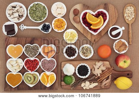 Superfood and herb selection for cold and flu remedy including foods high in antioxidants and vitamin c over grey background.