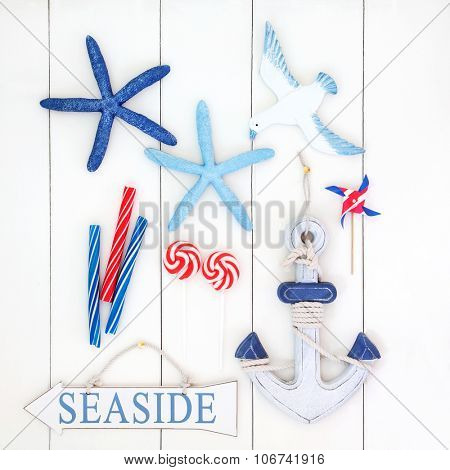 Abstract collage with seaside sign, decorative starfish, anchor, seagull, toy windmill and candy striped rock over white wooden  background.