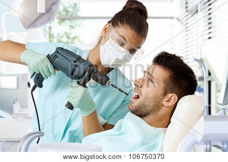 Aggressive female dentist drilling tooth with power drill.