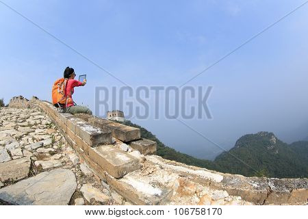 young woman hiker use digital tablet sit on chinese great wall