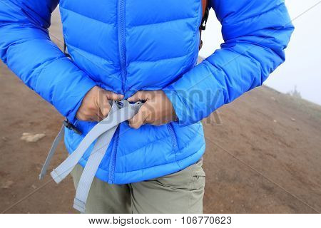 woman hiker buckle up the belt of backpack on mountain peak