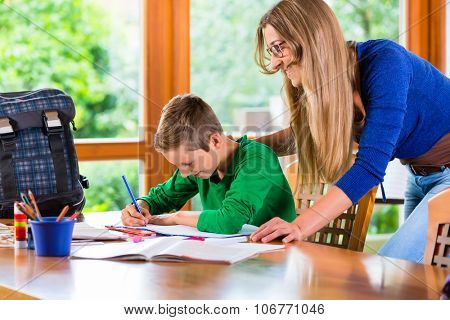 Mother helping son with school homework assignment for school at home