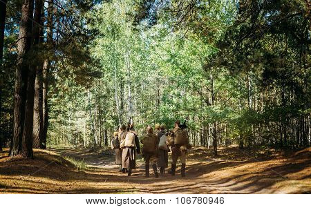 Group of unidentified re-enactors dressed as Soviet russian soldiers goes along forest road. poster