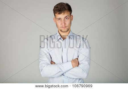 Young business man in white shirt spitefully and exactingly looks at his subordinates.