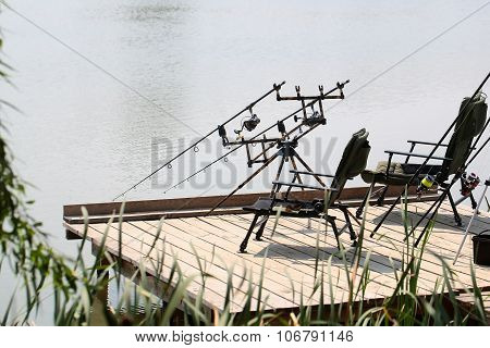 Armchairs With Fishing Tackle On Pier