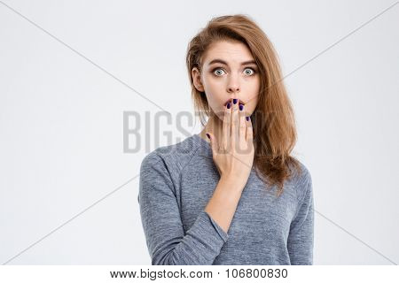 Portrait of amazed woman covering her mouth with palm isolated on a white background