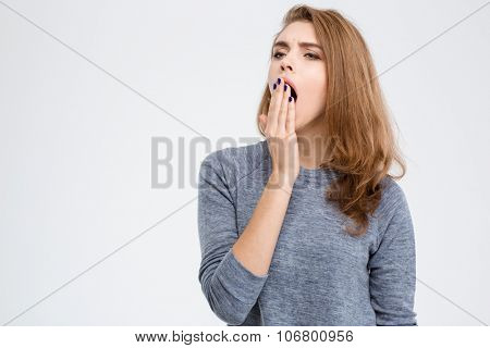 Portrait of a young woman yawning isolated on a white background