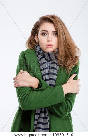 Portrait of a young beautiful woman in coat and scarf freezing isolated on a white background