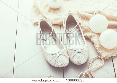 Flower girl silver glitter shoes closeup, selective focus, space for text
