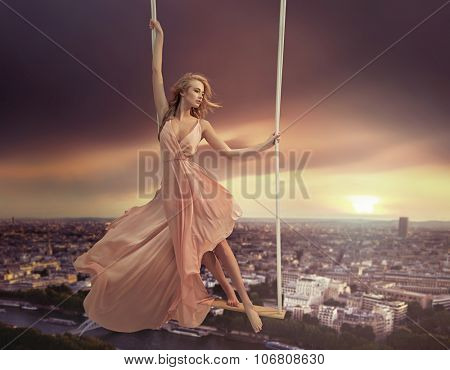 Attractive young lady on a swing above the city