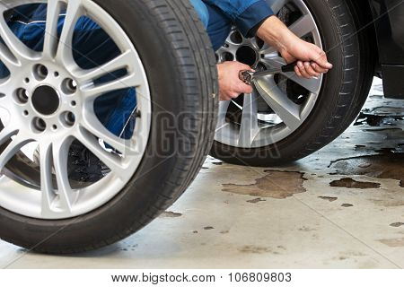 A mechanic tightening the wheel nuts on an alloy light weight rim after having exchanged summer tires for winter tires