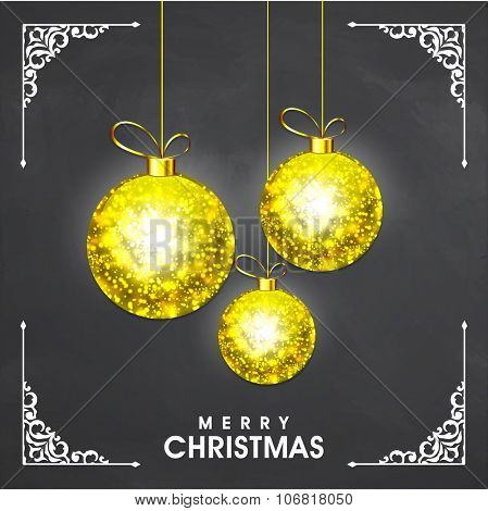Sparkling golden Xmas Balls hanging on shiny chalkboard background for Merry Christmas celebration.