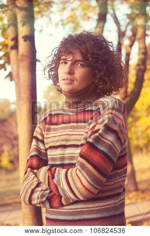 Attractive young man with long curly hair, dressed in striped sweater standing with his arms crossed in autumn park.
