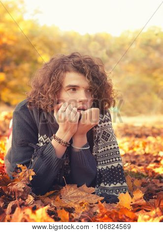 Stylish man in knit sweater and scarf lying on autumn leaves, oudoor in autumn park.
