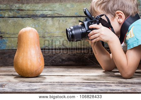 Funny Boy Trying To Take Photo Of Ripe Pumpkin