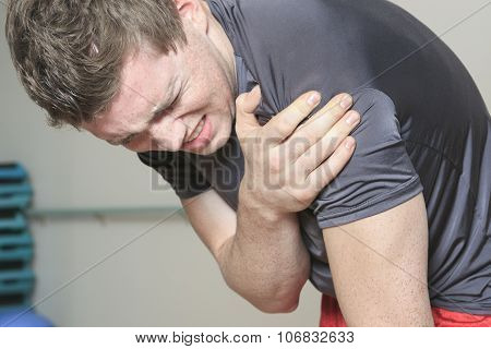 Portrait of a fitness man reaching for his knee in pain