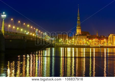 Saint Peter church, Stone Bridge and River Daugava in the Old Town of Riga at night, Latvia poster