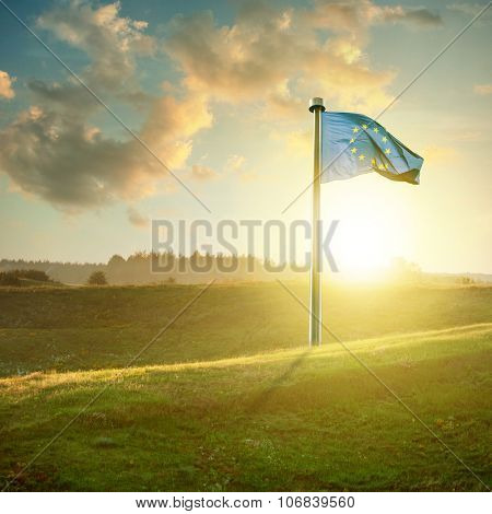 european union flag on sunset landscape with green field and beautiful clouds