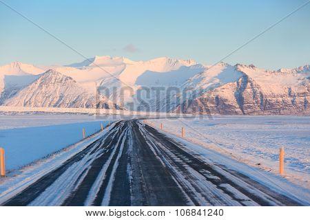 The road on a sunny day to the snow-capped mountains. The Ring Road (Route 1) of Iceland, between Hof and Jokulsarlon. South of Iceland