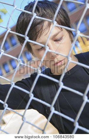 sad boy on a school playground closing