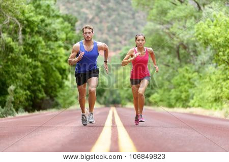 Determined man and woman running on road against trees. Runners sprinting in Full length of sporty male and female are in sports clothing. Athletic runner fitness sport couple are exercising outside. poster