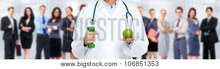 Hands of medical doctor woman with apple and dumbbell over people group background.