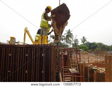 Construction workers pouring concrete slurry into reinforcement concrete wall formwork