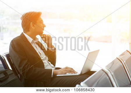 Business man using laptop while waiting his flight at airport, beautiful golden sunset background.