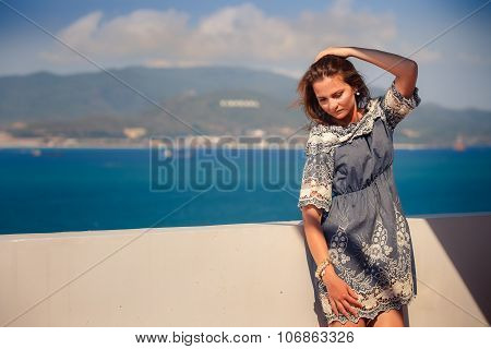 Brunette Girl In Short Grey Frock Leans On Wall Against Sea