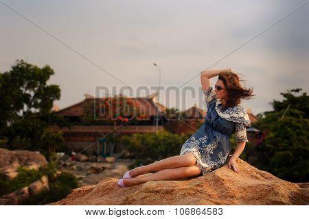 Brunette Girl In Short Grey Frock Sits On Rock Against Villas